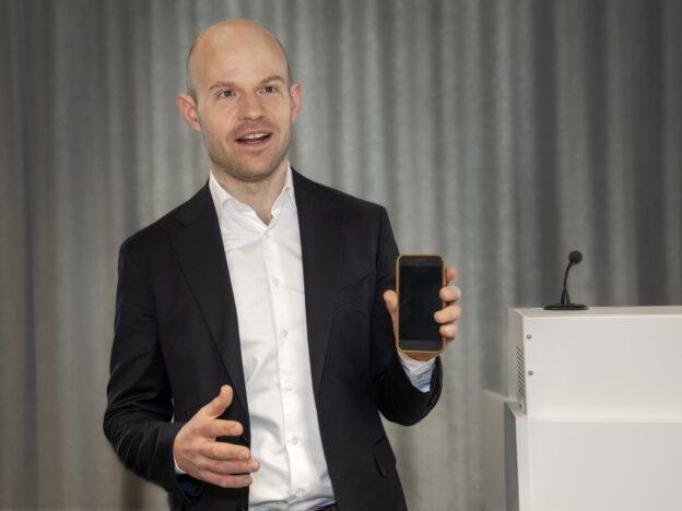 Johan Eriksson håller upp en telefon